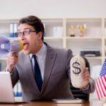 English-speaking business man at desk with an American flag, megaphone and back of money