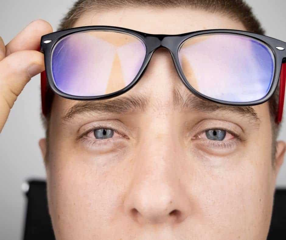 Man with Tired Eyes lifting up blue light glasses
