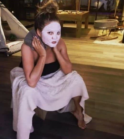 Chrissy Teigen vaginal steaming with a white face mask and heating pad on neck postpartum