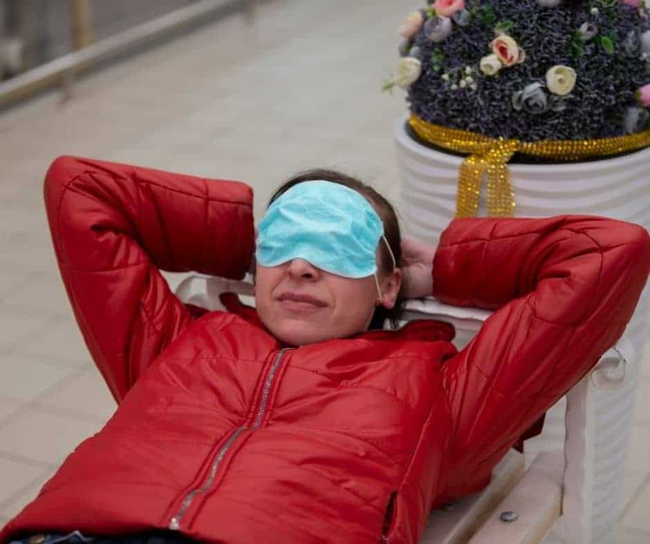 Woman lying on park bench with blue medical mask over her eyes