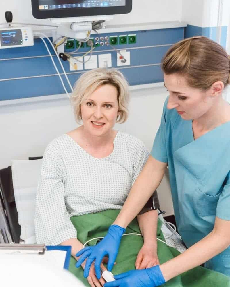 older woman in hospital post procedure