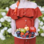 pregnant woman in a dress holding a plate full of apples, blueberries, strawberries and raspberries