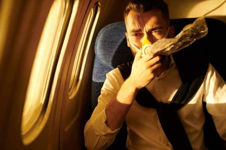Man on an airplane with an oxygen mask over his nose and mouth looking scared
