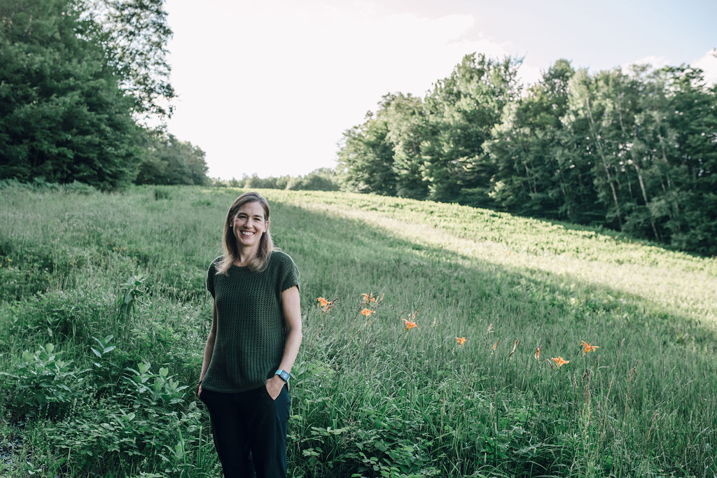 amy harris standing in a green field in vermont