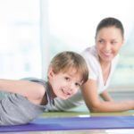 boy stretching with nanny on yoga mat