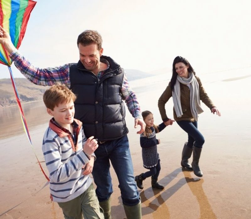 family of four at the beach flying a kite in winter
