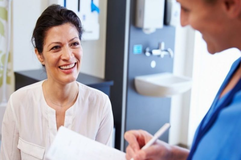 Woman at Doctor's Office with Doctor, taking notes