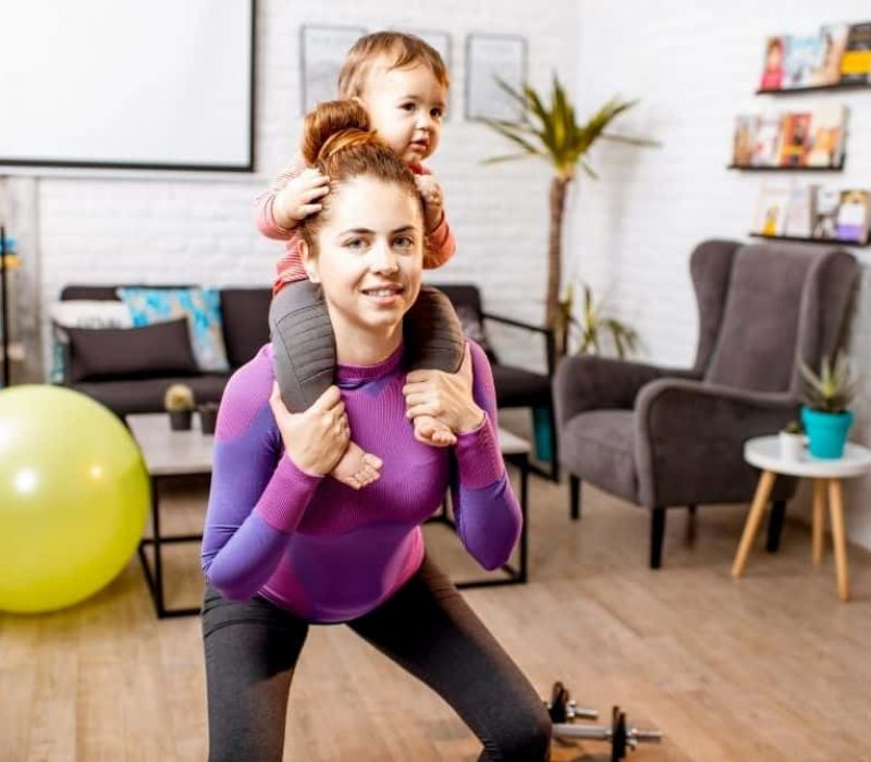 woman working out with child on her shoulders indoors