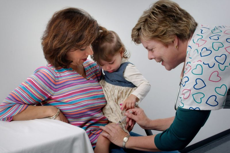 nurse vaccinating a toddler while in mother's lap