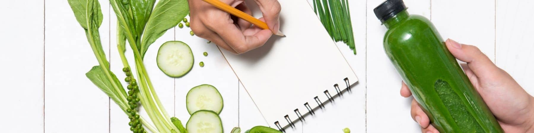 hand taking notes on a notepad with green drink and green fruits and vegetables