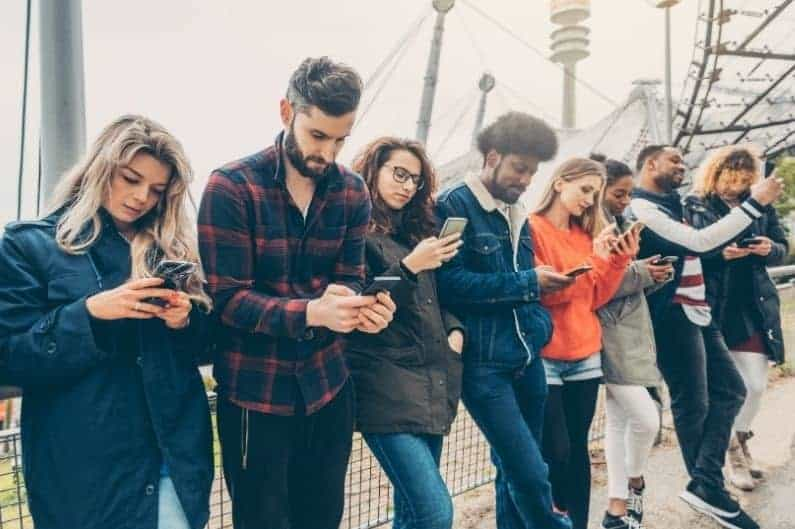 line of five young people all staring at their smartphones